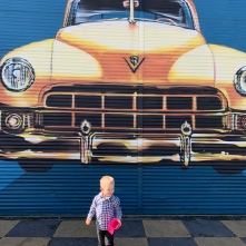 Who is this cute little guy standing in front of the street art?